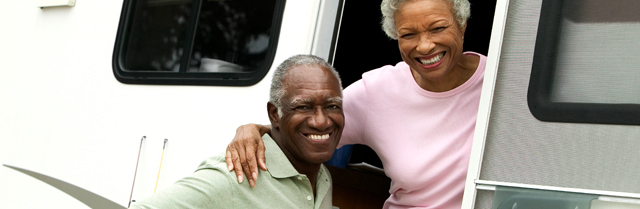 older couple smiling from the doorway of RV