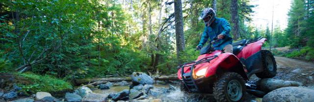 person crossing a creek riding on an all terrain vehicle