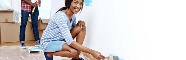 woman painting a wall and smiling